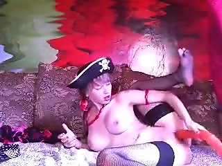 Sexnika, dressed as a pirate, plays with a rubber dildo